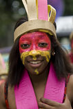 Una muchacha con una cara pintada, desgastando un tocado Fotos de archivo libres de regalías