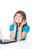 Una muchacha con una computadora portátil está escuchando la música Foto de archivo libre de regalías