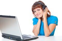 Una muchacha con una computadora portátil está escuchando la música Fotografía de archivo
