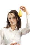Una muchacha con una fruta en su mano Foto de archivo libre de regalías