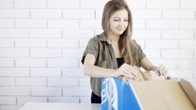 Una muchacha concentrada los jóvenes abre un regalo de la caja Imágenes de archivo libres de regalías