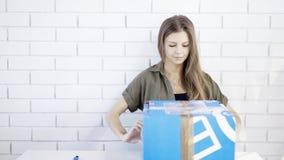 Una muchacha concentrada los jóvenes abre un regalo de la caja Fotos de archivo libres de regalías