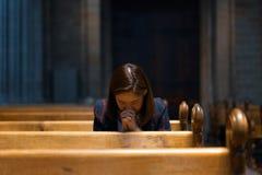 Una muchacha cristiana es que se sienta y de rogación con el corazón quebrado en Imágenes de archivo libres de regalías