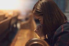 Una muchacha cristiana es que se sienta y de rogación con el corazón quebrado en Fotografía de archivo libre de regalías