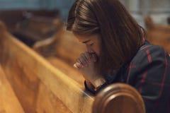 Una muchacha cristiana es que se sienta y de rogación con el corazón quebrado en Imagen de archivo