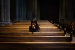 Una muchacha cristiana es que se sienta y de rogación con el corazón quebrado en Fotos de archivo