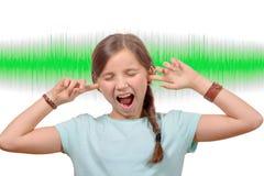 Una muchacha cubre sus oídos, onda acústica en fondo Imagenes de archivo