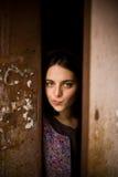 Una muchacha curiosa joven mira hacia fuera de detrás la puerta de su casa Ella piensa en ir afuera Concepto de la agorafobia Foto de archivo