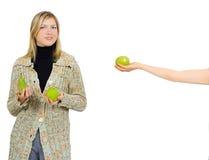 Una muchacha da una manzana a una otra Imagen de archivo