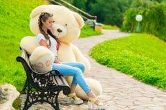 Una muchacha de 20 años en un parque con su oso de peluche enorme Foto de archivo