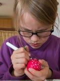 Una muchacha de 7 años está pintando un huevo punteado rojo para pascua foto de archivo
