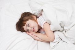 Una muchacha de 4 años que sonríe en la cama blanca Fotografía de archivo