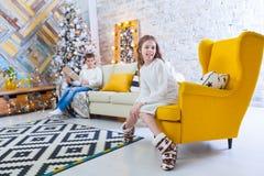 Una muchacha de 10 años se sienta en una silla amarilla en la casa antes de los días de fiesta de la Navidad En el fondo un mucha Imágenes de archivo libres de regalías