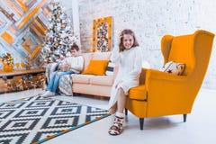 Una muchacha de 10 años se sienta en una silla amarilla en la casa antes de th Fotos de archivo