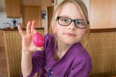 Una muchacha de 7 años sonríe y sostiene un huevo de Pascua en la cámara foto de archivo