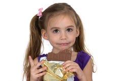Una muchacha de cuatro años come el chocolate y hace un gesto Fotografía de archivo