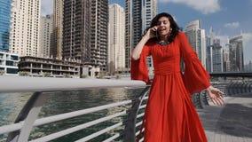 Una muchacha de la raza mixta en un vestido rojo brillante camina a lo largo del puerto deportivo de Dubai y admiringly de hablar almacen de video