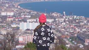 Una muchacha de las miradas de la montaña en la ciudad almacen de metraje de vídeo