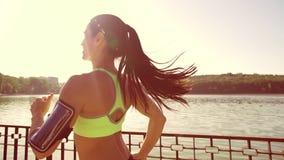 Una muchacha de los deportes corre a través del parque por el lago Visión desde el behin almacen de metraje de vídeo