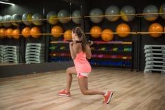 Una muchacha de los deportes que hace ejercicios de pierna en un fondo del gimnasio Hembra joven apta con un palillo de la aptitu Fotos de archivo libres de regalías