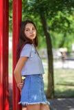 Una muchacha de moda en inconformista de moda viste en un fondo natural borroso Moda, al aire libre, concepto de la juventud Copi Fotos de archivo libres de regalías