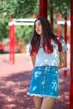Una muchacha de moda en inconformista de moda viste en un fondo natural borroso Moda, al aire libre, concepto de la juventud Copi Foto de archivo