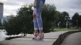 Una muchacha de moda vestida promenading cerca de un río en un tiempo ventoso almacen de video