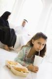 Una muchacha de Oriente Medio que goza de los alimentos de preparación rápida Imagen de archivo
