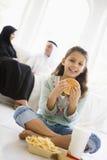 Una muchacha de Oriente Medio que goza de los alimentos de preparación rápida Imagen de archivo libre de regalías
