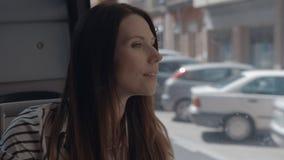Una muchacha de pelo largo que se sienta en un autobús y que mira fuera de la ventana almacen de metraje de vídeo
