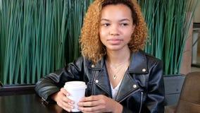 Una muchacha de piel morena joven hermosa en una chaqueta de cuero está bebiendo el café de un vidrio blanco en un café en un ver almacen de metraje de vídeo
