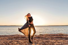 Una muchacha de un cuerpo deportivo camina en la danza y camina a lo largo de la playa arenosa en el amanecer del sol en la ropa  imagenes de archivo
