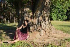 Una muchacha debajo del árbol Imagenes de archivo