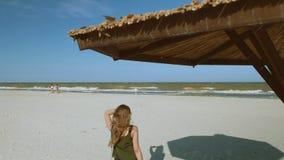 Una muchacha defiende en una playa abandonada el parasol de playa hecho de las cañas metrajes