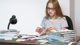 Una muchacha del adolescente con los vidrios se está sentando en un escritorio de la escuela Aprendizaje de concepto almacen de metraje de vídeo