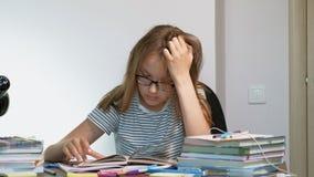 Una muchacha del adolescente con los vidrios se está sentando en un escritorio de la escuela Aprendizaje de concepto metrajes