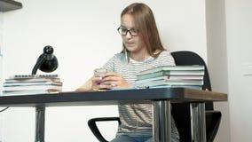 Una muchacha del adolescente con los vidrios se está sentando en un escritorio de la escuela Aprendizaje de concepto almacen de video