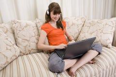 Una muchacha del adolescente que habla con un receptor de cabeza en una computadora portátil Fotos de archivo libres de regalías