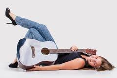 Una muchacha del adolescente que pone en la tierra con la guitarra Foto de archivo libre de regalías