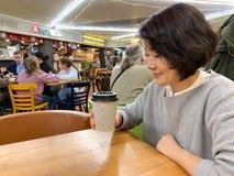 Una muchacha del café agradable de las bebidas del aspecto de una taza de papel imagenes de archivo