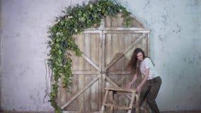 Una muchacha del florista mueve una pequeña escalera en un fondo hermoso almacen de metraje de vídeo