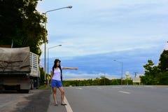 Una muchacha del viajero en el control blanco de la camisa un mapa y agitar su mano Foto de archivo