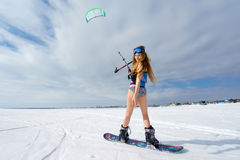 Una muchacha delgada en un bañador en el invierno Snowboard y Foto de archivo
