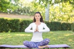 Una muchacha delgada está pareciendo deportiva y está haciendo deportes y ejercicio de la yoga Una deportista encantadora imagen de archivo