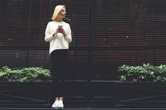 Una muchacha delgada hermosa que se coloca cerca del café y que habla en el teléfono y esperas para su novio Fotografía de archivo