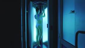 Una muchacha delgada lujosa se coloca en un solarium vertical y toma el sol Muchacha atractiva en soportes de la ropa interior co almacen de metraje de vídeo