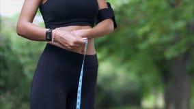 Una muchacha delgada mide su cintura con un centímetro almacen de metraje de vídeo