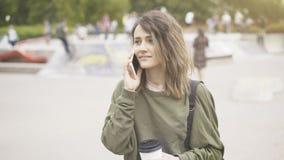 Una muchacha deliciosa joven está caminando en el parque que tiene una llamada Fotos de archivo libres de regalías