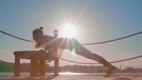 Una muchacha deportiva hace los pectorales Contratan a la mujer joven delgada y atl?tica a deportes al aire libre en la calle almacen de metraje de vídeo