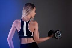 Una muchacha deportiva lleva a cabo una pesa de gimnasia en sus manos, sacude un muscular Contra un fondo oscuro Imagenes de archivo